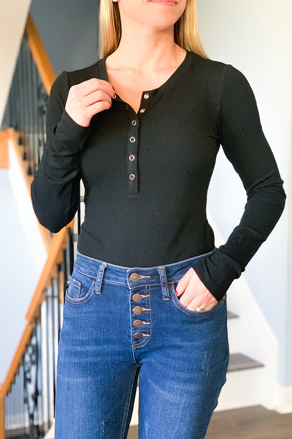 Our Ribbed Long Sleeve Henley Bodysuit in Black is a must-have for an easy and effortless outfit!  This super soft, ribbed knit bodysuit will keep you feeling comfy while still looking chic! Featuring front silver snap closure, fitted body, fitted long sleeves, and a thong bottom with two snap closures.  This quality, bodysuit is lightweight and has an amazing amount of stretch but no need to worry about it being see through.  This bodysuit is perfect!  Great for layering.