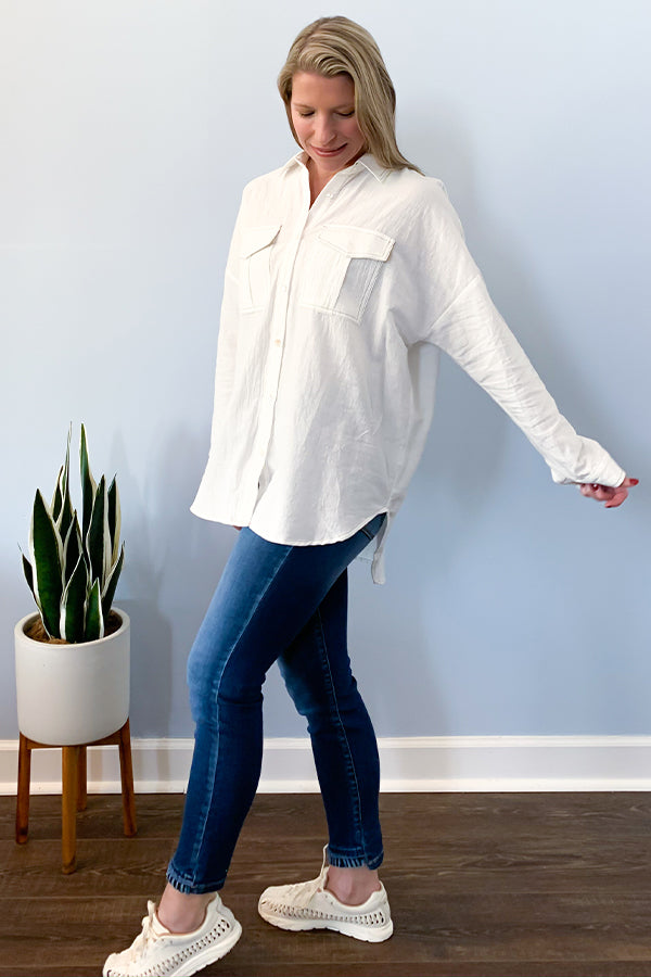 Lightweight White Button Down Blouse With Cutout Back.  This solid woven button down top features a collared neckline, button chest pockets, and drop shoulder hem.  The loose fit will keep you feeling comfortable while still standing out with it's contrasting outline stitches and v cutout back.  The long sleeves are cuffed with button closures and a curved dolphin hemline. Promesa blouse.