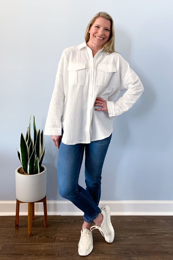 Lightweight White Button Down Blouse With Cutout Back.  This solid woven button down top features a collared neckline, button chest pockets, and drop shoulder hem.  The loose fit will keep you feeling comfortable while still standing out with it's contrasting outline stitches and v cutout back.  The long sleeves are cuffed with button closures and a curved dolphin hemline.