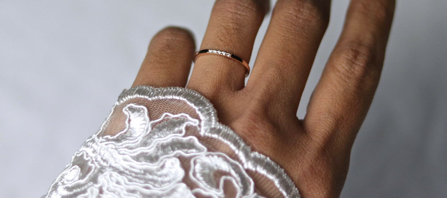 rose gold and diamond wedding ring on hand with lace sleeve