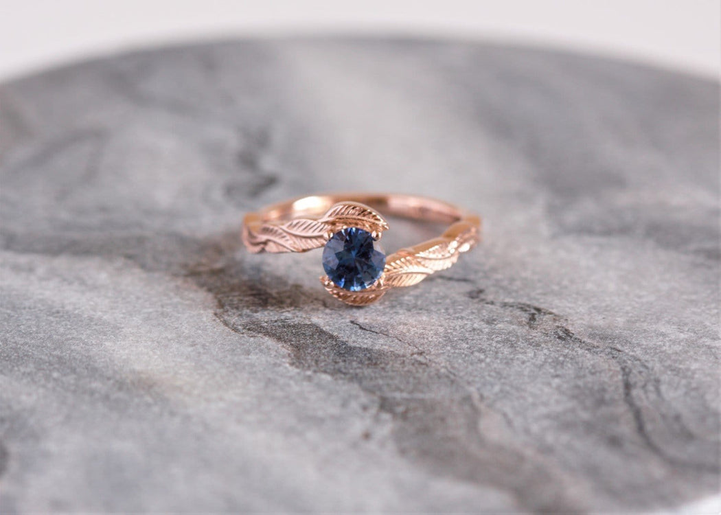blue sapphire engagement ring on granite background
