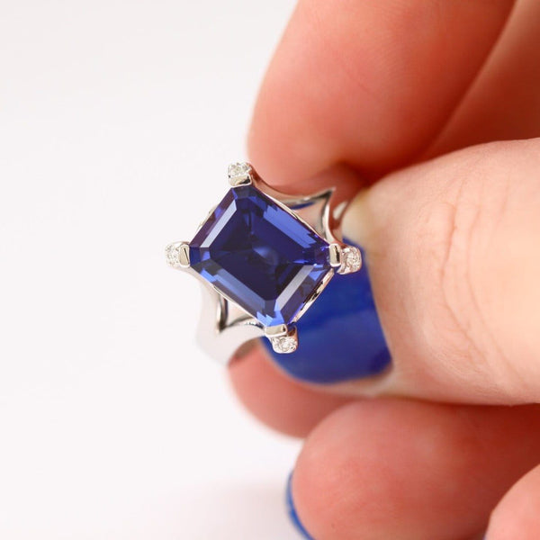 blue sapphire and diamond ring between fingers