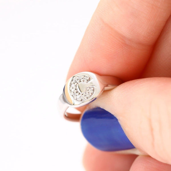 diamond pinky signet ring between fingers