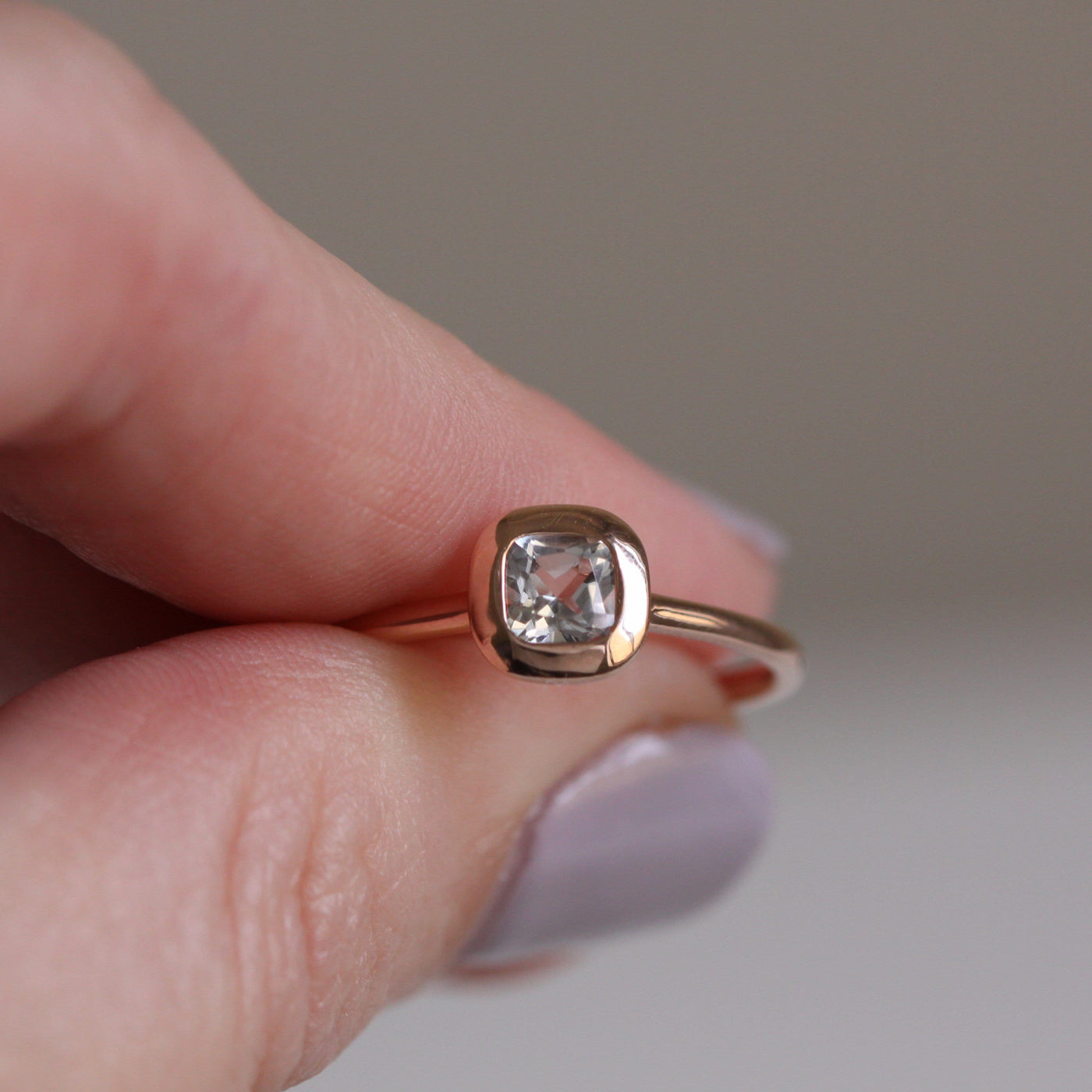fingers holding rose gold ring with white topaz centre stone