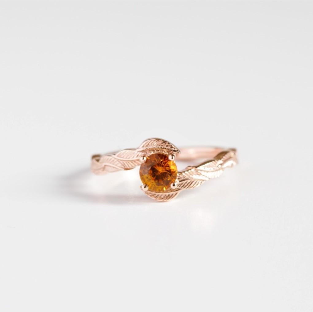 orange sapphire engagement ring on white background