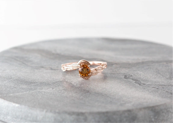 rose gold orange sapphire engagement ring on granite background