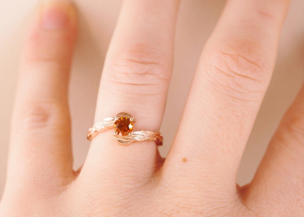 rose gold orange sapphire engagement ring on hand
