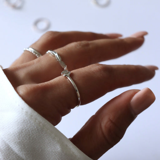 white gold rings on woman's hand