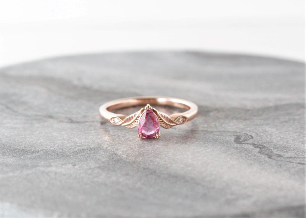rose gold pink sapphire engagement ring on granite background