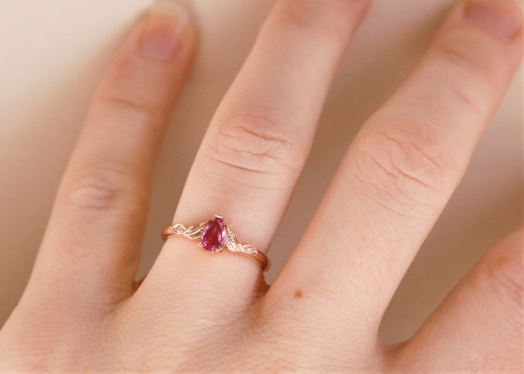 rose gold pink sapphire engagement ring on hand
