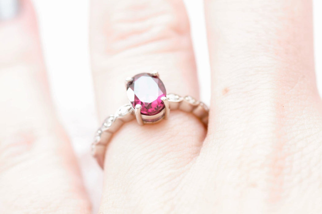 rhodolite garnet and diamond engagement ring on finger