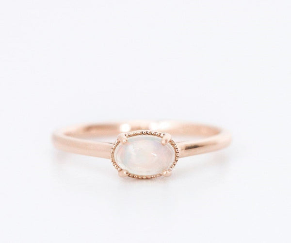 rose gold opal engagement ring on white background