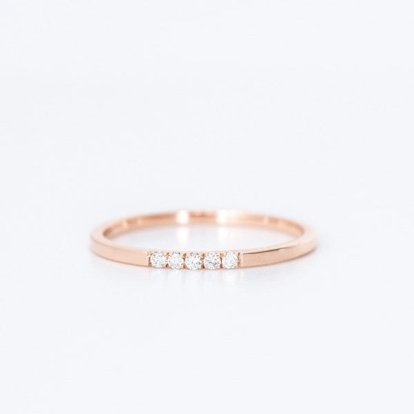 five diamond rose gold wedding band on white background