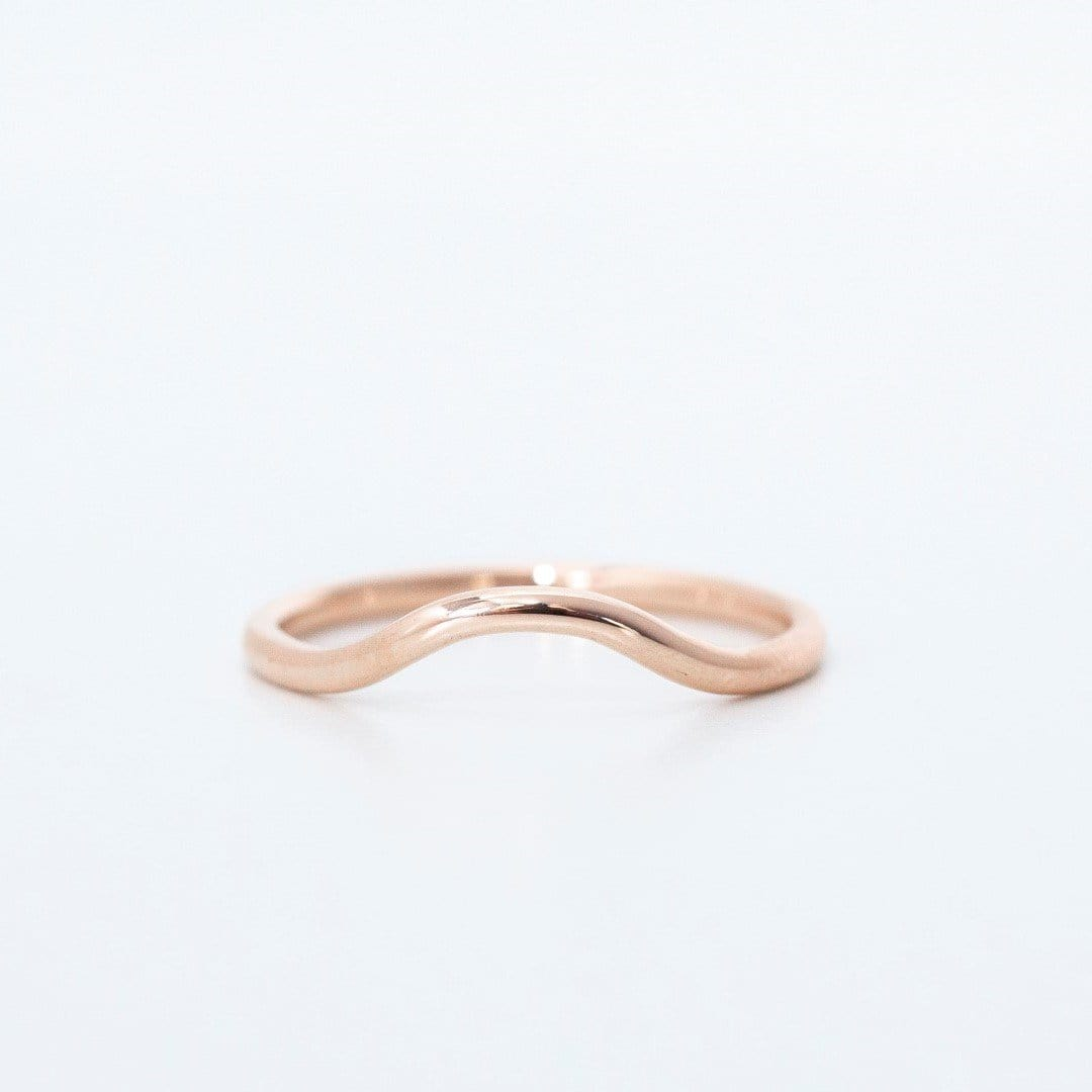 rose gold curved wedding band on white background