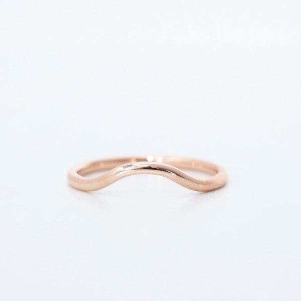rose gold curved wedding ring on white background