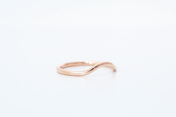 rose gold curved wedding band on white background side