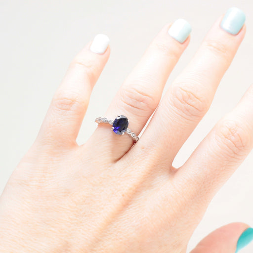 blue sapphire and diamond engagement ring on hand