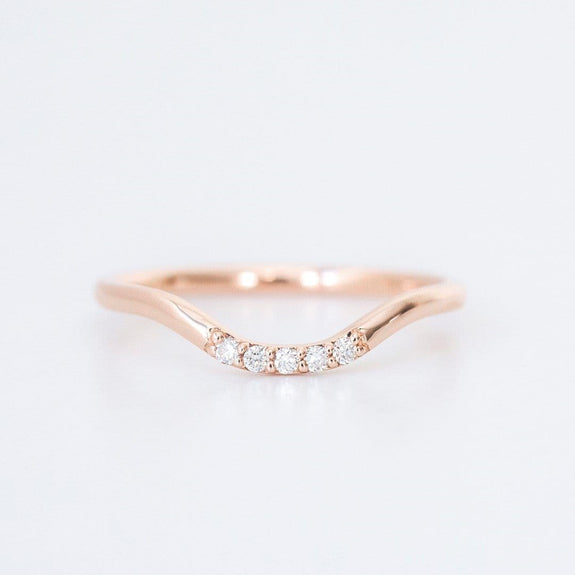 rose gold and diamond curved wedding band on white background
