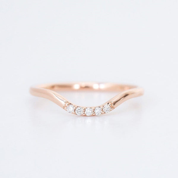 rose gold and diamond curved wedding ring on white background