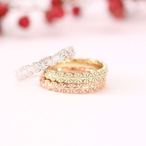 rose gold, white gold and yellow gold daisy eternity rings stacked on white background