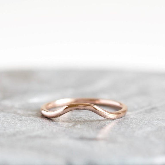 rose gold curved wedding band on granite background