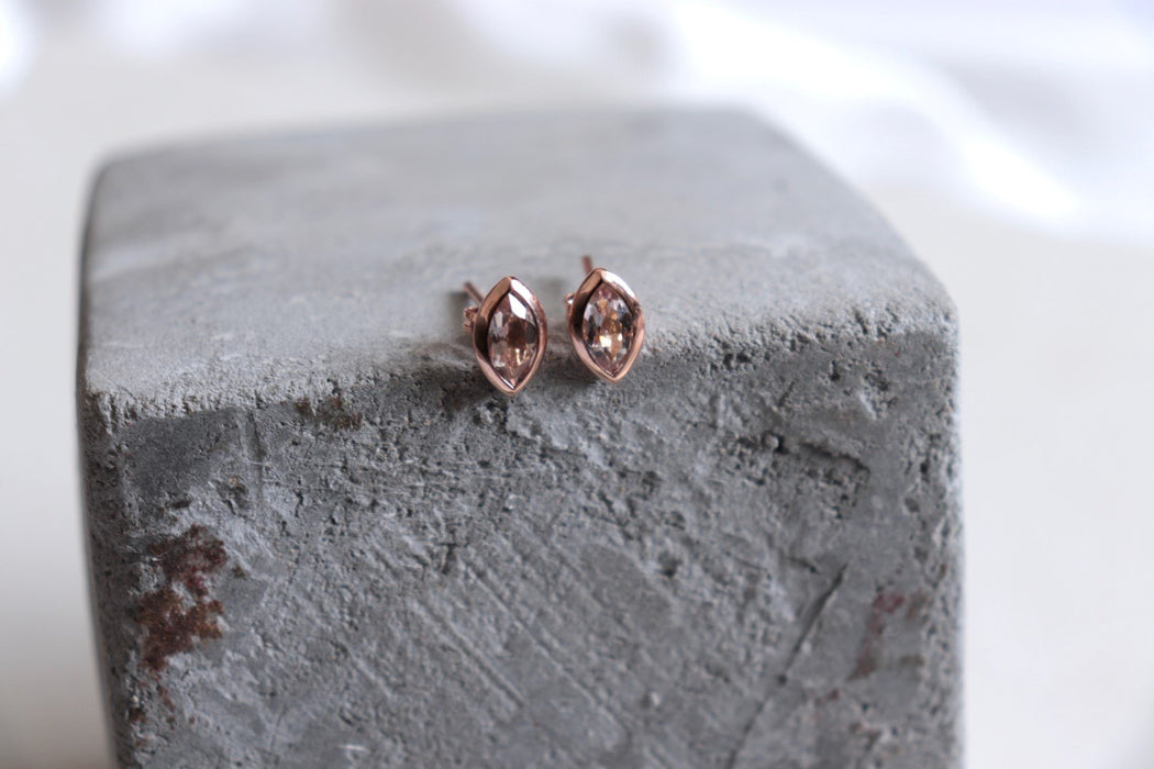 rose gold earrings on concrete with silk background