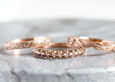 rose gold nepalese patterned wedding ring and others on granite background