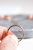 rose gold nepalese patterned wedding ring between fingers