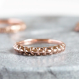 rose gold nepalese patterned wedding ring on granite background