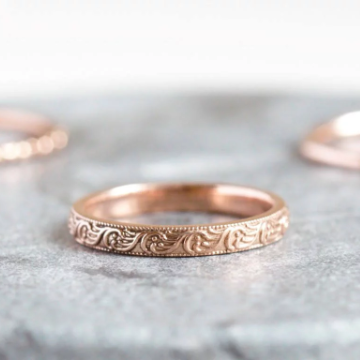 rose gold patterned ring on granite background