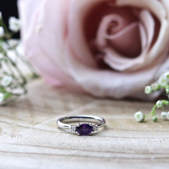 purple amethyst and diamond white gold engagement ring on wooden background