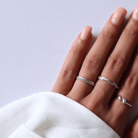 white gold stacking ring on hand with other rings