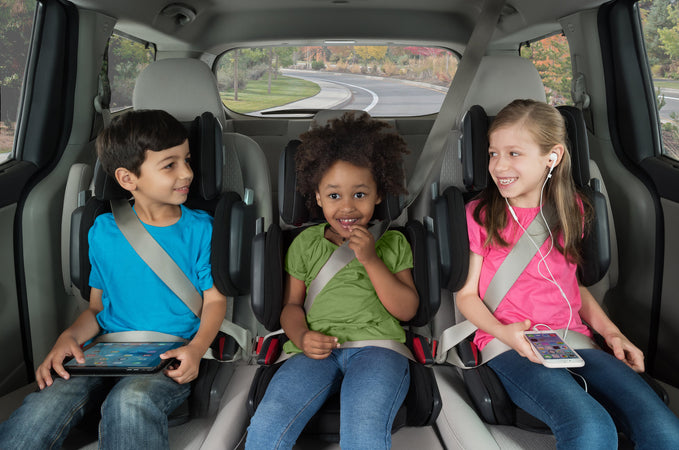 three children in their hifold booster seats