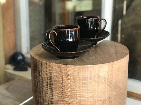 Two small coffee cups with saucers