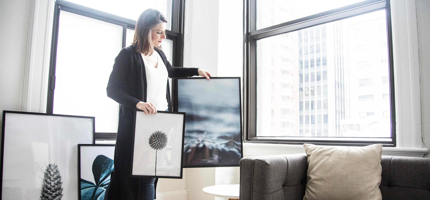 Our Story | Opposite Wall President holds two modern art photography framed posters in their Montreal office