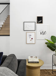 Scandinavian poster by Opposite Wall with black and white graphic typography design of Le tourbillon de la vie - Living room with a gallery wall