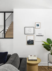 Scandinavian poster by Opposite Wall with black and white graphic typography design of tout est possible - Living room with gallery wall quadruple