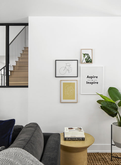 Scandinavian poster by Opposite Wall with black and white graphic typography design of Aspire to Inspire - Living room with Gallery Wall