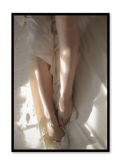 """Between the Sheets"" is a minimalist beige and white photography poster by Opposite Wall of a woman's nude legs, and feet in white bed sheets."