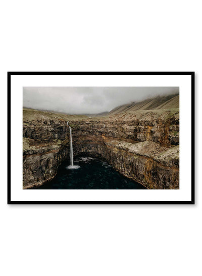 'Nebulous' is a landscape photography poster by Opposite Wall of a small waterfall rushing down a wide rocky cliff toward the calm water of a lake.