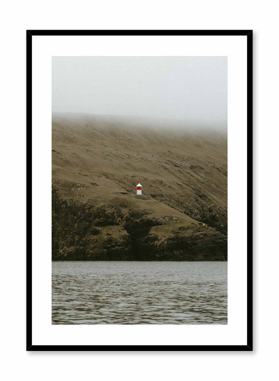 'Lone Lighthouse' is a landscape photography poster by Opposite Wall of a red and white lighthouse over foggy lush green hills overlooking the water.