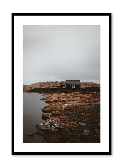 'Lakeside View' is a landscape photography poster by Opposite Wall of a quaint cottage style house on orange and brown grass overlooking a quiet lake under a cloudy grey sky.