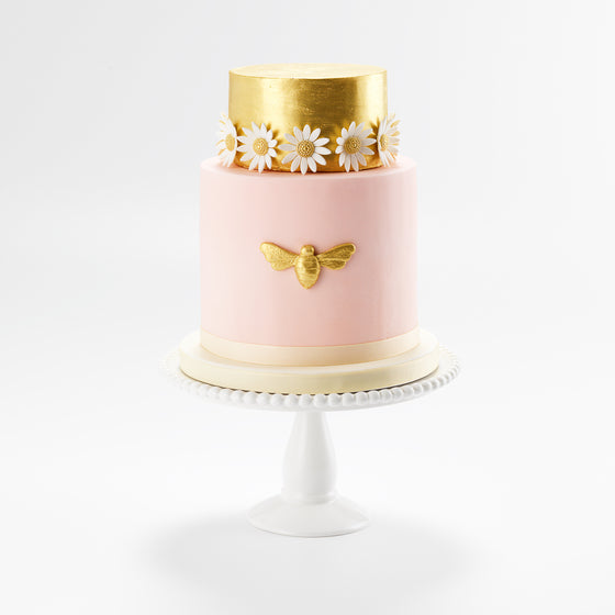 Decorated with a handmade golden sugar bee and white sugar daisies, this two tier celebration cake, suitable for any ocasion, serves 40 portions, and is ready to be delivered in 2 days