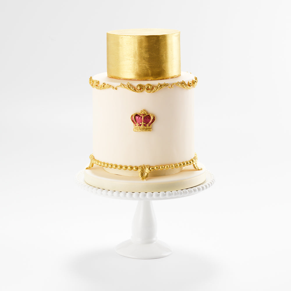 This beautiful two tier celebration cake decorated with ornate gold moulding, and a regal crown serves 40 portions