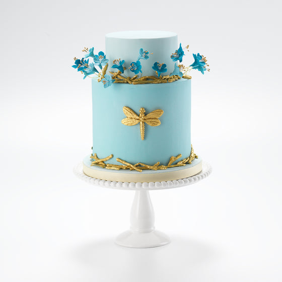 Golden sugar paste twigs litter the bottom tier of this golden dragonfly celebration cake, ideal for a birthday cake. While lovingly crafted edible sugar flowers grow out, like a wild meadow, from soft blue iced fondant.