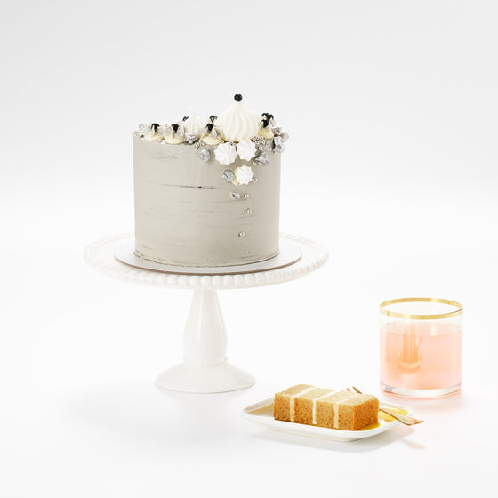A  grey marbled buttercream salted caramel cake which is topped with tumbling meringue clouds and silver popcorn