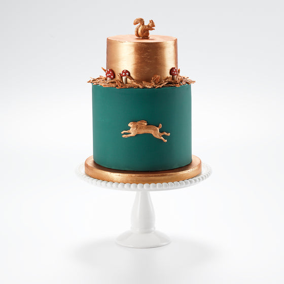 An autumnal forest cake, ideal for a mans birthday cake. It has a metallic copper top tier, with details of a copper sugar squirrel and hare nestling amongst autumn sugar leaves