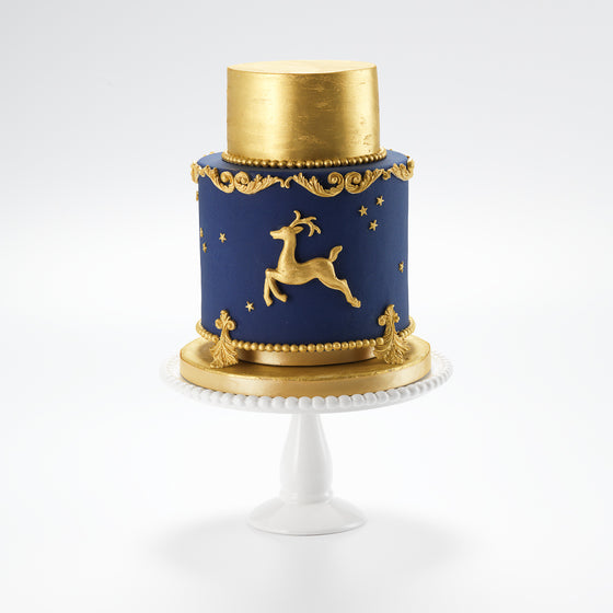 A dreamy festive Christmas cake, decorated with a golden sugar reindeer, and golden stars twinkling on a deep blue night sky