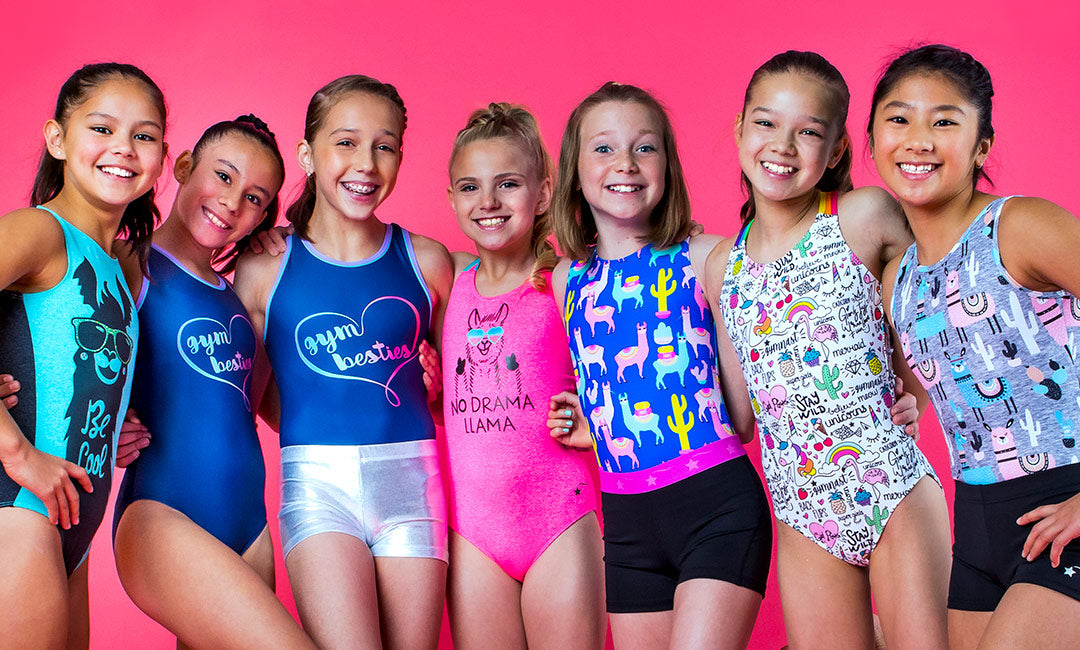 A group of seven girls wearing Destira leotards and shorts on a solid bright pink background.