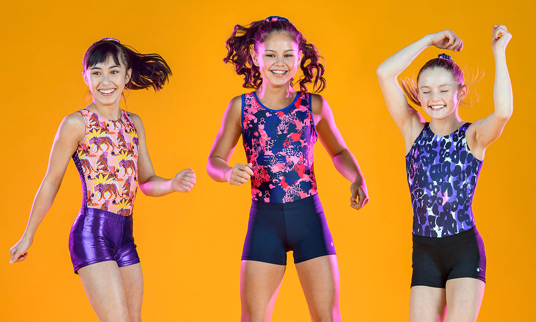 Three happy girls dancing in leotards and shorts on a solid yellow background